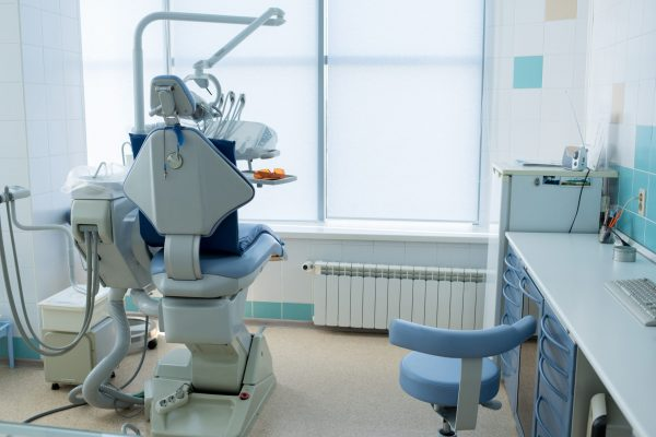 Interior of contemporary light office with working seat and desktop of dentist.